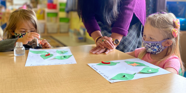 children doing nature based crafts with paper leaves