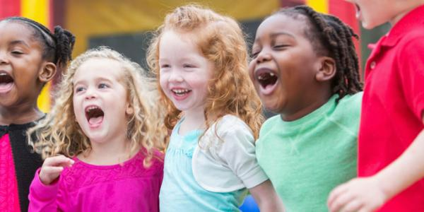 Group of five diverse children playing outdoors