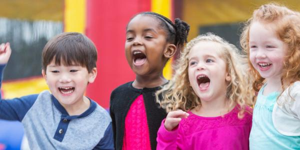 Group of children from different backgrounds singing or shouting during a game with smiles on their faces.