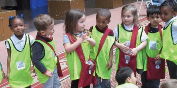 Children standing in a line and wearing safety vests