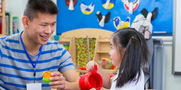 Teacher and young child interact in play.