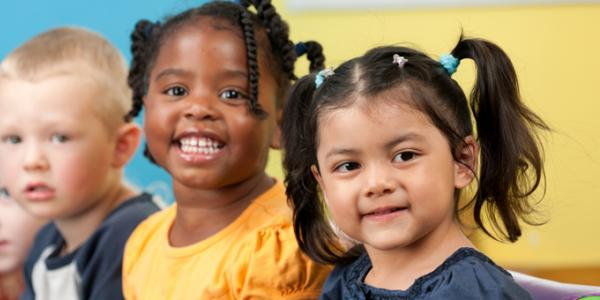 Group of five diverse children smiling