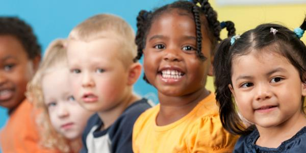 Five diverse preschool-aged children smiling at camera