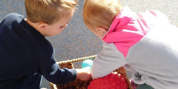 Two children look through a basket of balls.