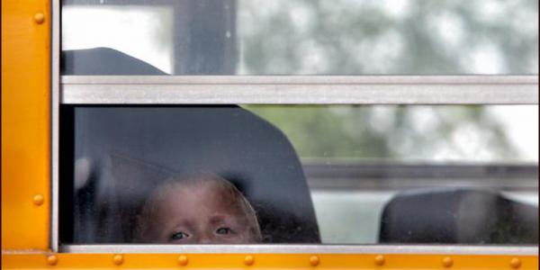 Little boy looking outside of school bus window