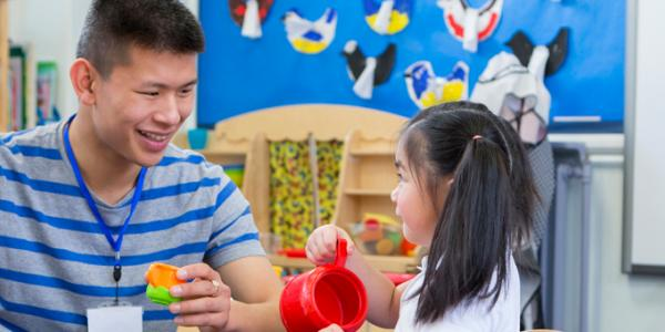 Asian male and young girl interact in the dramatic play area