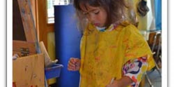 Child with paint smock on, standing near easel and paint containers.