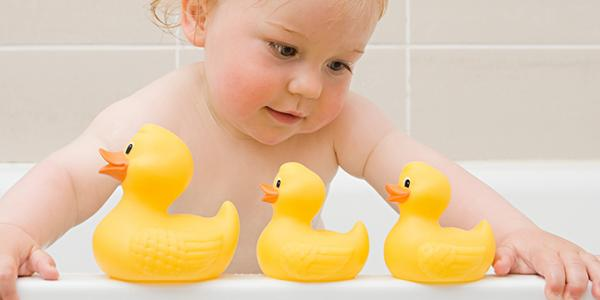 Toddler in the bathtub playing with rubber ducks.