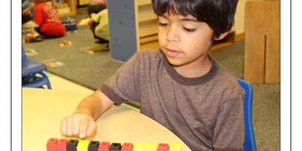 Boy sitting at table playing with small, multicolored blocks