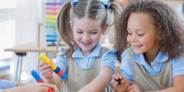 Two preschool girls in a classroom laughing