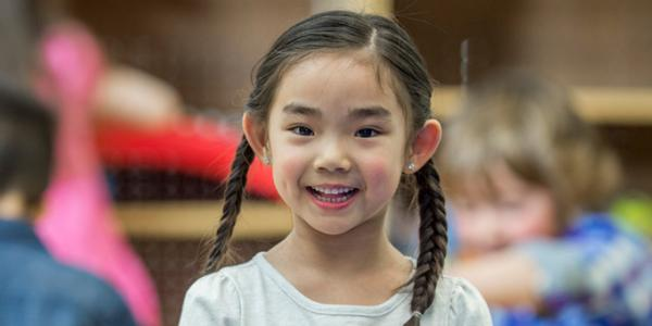 Asian girl in class smiling at camera