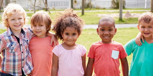 Seven young children pose for an outdoor picture