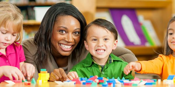 Teacher smiling with 3 young children playing blocks