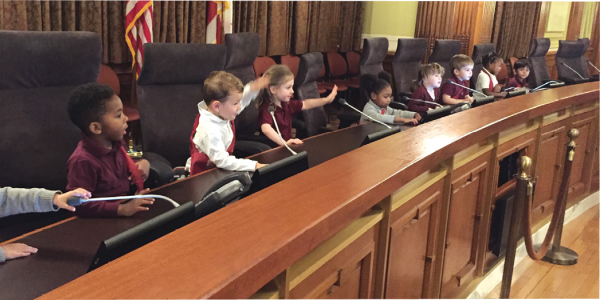 A group of preschool children sits at a city hall desk.