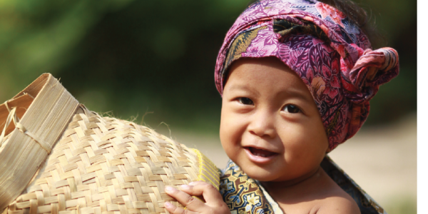Young child in Indonesia with basket and colorful headscarf