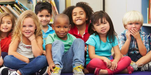 A diverse group of young children looking forward to a read aloud