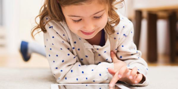 A young child draws on a tablet