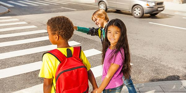 Three children of different races and ethnicities walk to school together.