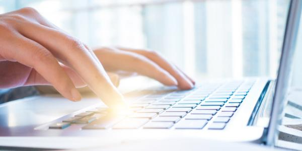 A picture of someone typing on a laptop
