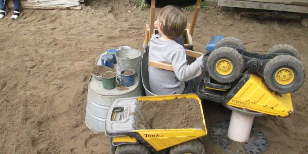 Child in poop machine in outdoor sandbox