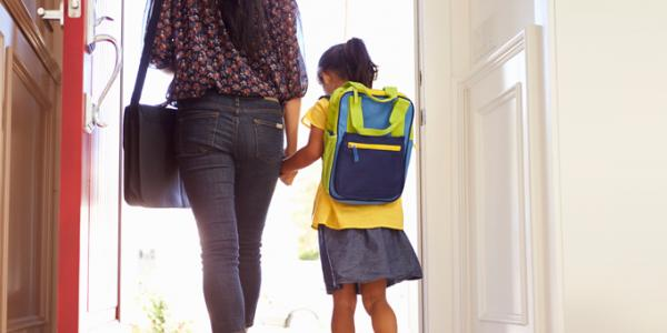 A young girl with a backpack walks through a door with her parent.  Both are seen from behind.