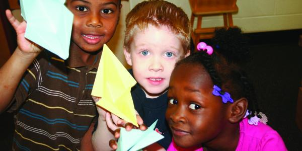 Three children hold up their paper animal creations.