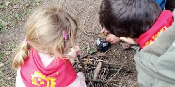 One child watches as another child pretends to build a fire.