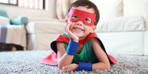 preschool boy dressed in a superhero cape and mask