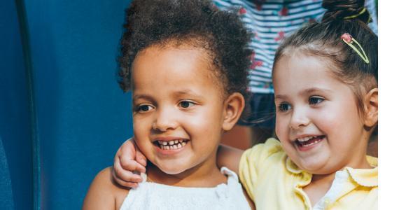 Two preschool girls sitting side by side hugging