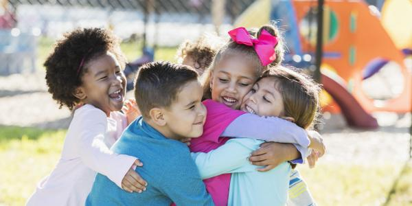 Group of diverse young children hugging on the playground