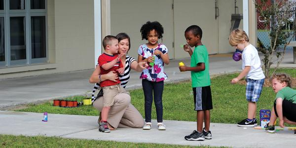 teacher with students on playground