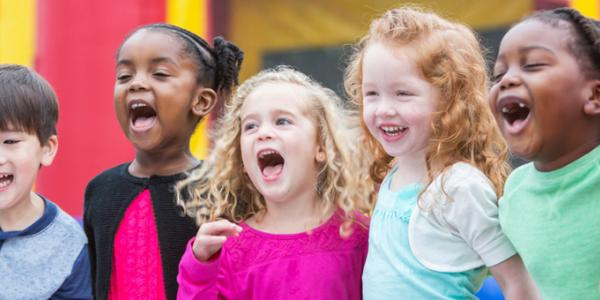 Group of five preschoolers laughing and smiling outdoors