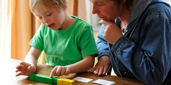 Mother and son reading cards and counting blocks