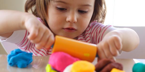 young girl rolling playdough