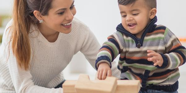 An adult woman helps a young male child with blocks.