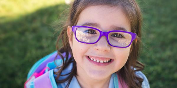 A young child with glasses smiling.
