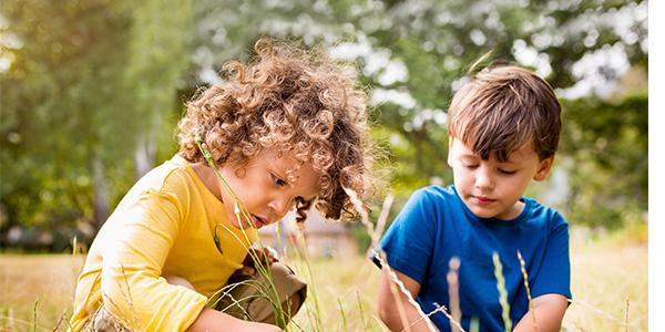 Young children exploring in the grass outside.