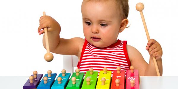A baby playing on a toy xylophone.