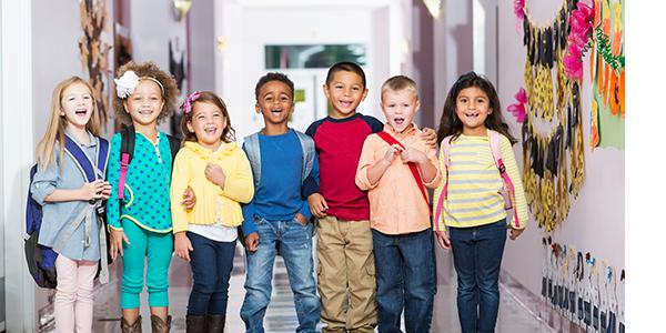A diverse group of young children with backpacks.