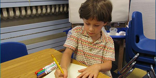 A young child at a desk writing on a piece of paper.