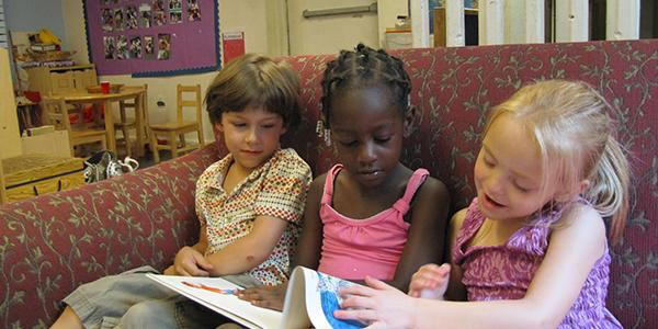 A group of children reading a book on a sofa together.