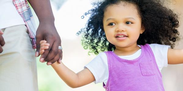 Young girl outside holding hands with parents