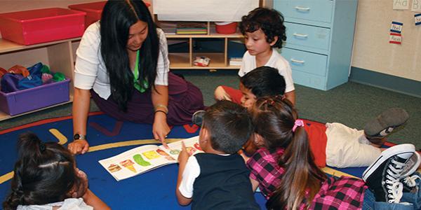 Preschool teacher showing students a picture book