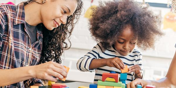 Girl building a structure while her teacher observes