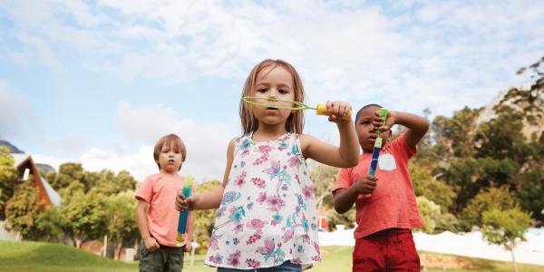 Children blowing bubbles in field