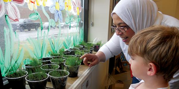 Teacher and child looking at indoor plants