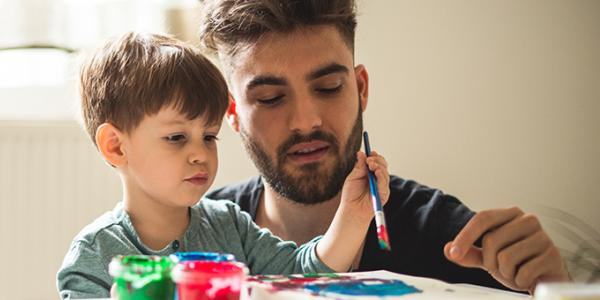 Young adult male painting with a preschool boy