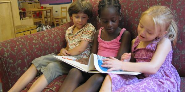three preschoolers in a classroom sitting on a chair reading a book
