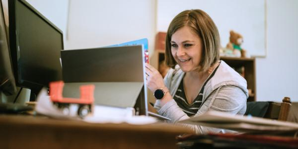 A teacher smiling at a computer