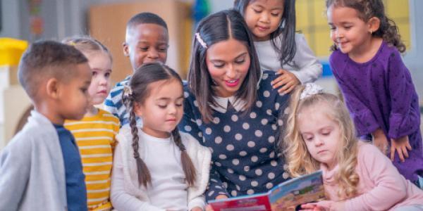 teacher with children gathered around a book